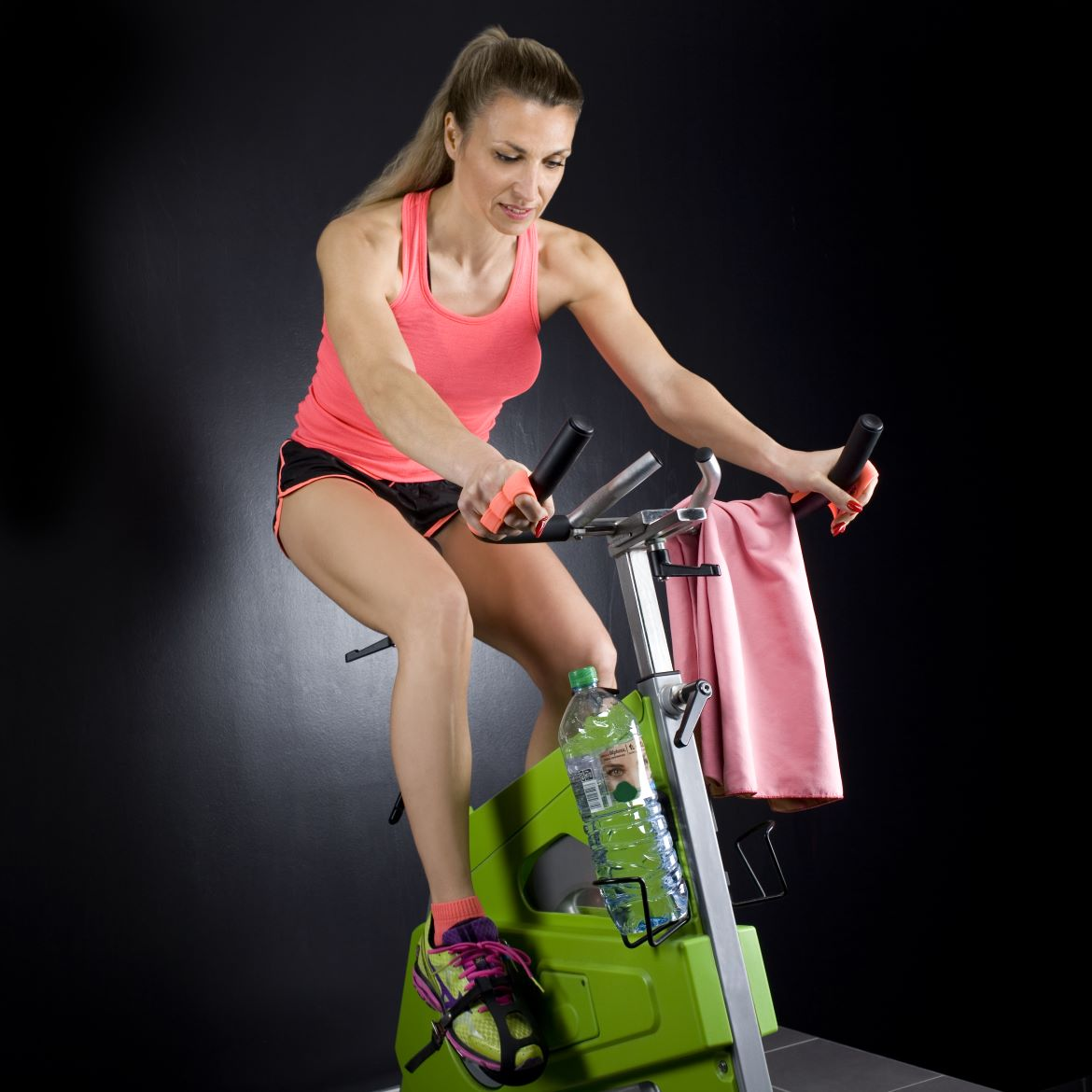 Corinne on the rpm lesmills bike with a pair of powerhand air